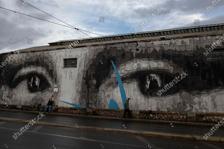 Two men wearing face masks to prevent the spread of the coronavirus walk past a giant mural by Greek street artist iNO depicting the eyes of Leonardo da Vinci's Mona Lisa, in Athens, . Greece is expected to see a 10.5% contraction of its gross domestic product this year, above the forecasted EU average of 7.4%, while its debt-to-GDP ratio is set to surge to a staggering 208.9% according to the EU and Greek authorities