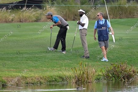 Vijay Singh, center, of Fiji Islands, lines up a putt with his son Qass on the 17th green during the first round of the PNC Championship golf tournament, in Orlando, Fla