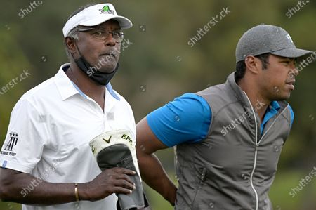Vijay Singh, left, of Fiji Islands, and his son Qass walk on the 18th fairway after hitting their tee shots during the first round of the PNC Championship golf tournament, in Orlando, Fla