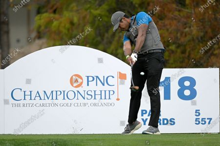 Qass Singh, son of golfer Vijay Singh, hits his tee shot on the 18th hole during the first round of the PNC Championship golf tournament, in Orlando, Fla