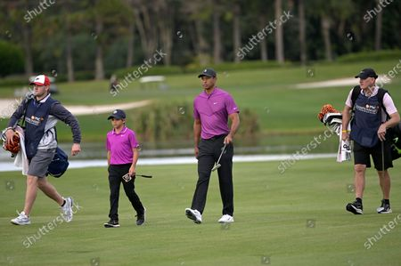 Tiger Woods, second from right, and his son Charlie walk on the 16th fairway with their caddies Joe LaCava, right, and Joe LaCava Jr., left, during the first round of the PNC Championship golf tournament, in Orlando, Fla
