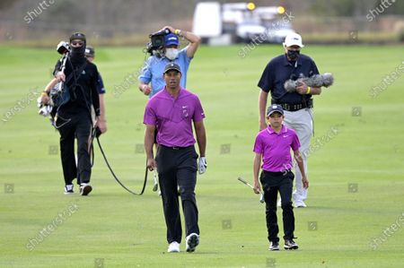 Tiger Woods, left, and his son Charlie walk on the 15th fairway during the first round of the PNC Championship golf tournament, in Orlando, Fla