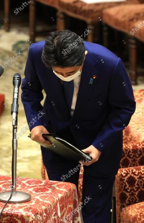Former Japanese Prime Minister Shinzo Abe bows his head upon his arrival at Lower House's house management committee session as he apologizes his false statements to parliament at the National Diet in Tokyo on Friday, December 25, 2020. Prosecutors decided not to indict Abe for his alleged case of illegal payment and prosecutors ended investigation of Abe's scandal.