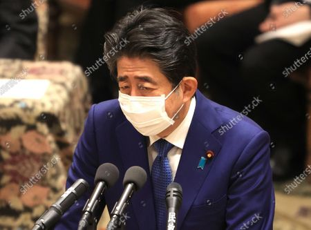 Former Japanese Prime Minister Shinzo Abe answers a question as he apologizes his false statements to parliament at Lower House's house management committee session at the National Diet in Tokyo on Friday, December 25, 2020. Prosecutors decided not to indict Abe for his alleged case of illegal payment and prosecutors ended investigation of Abe's scandal.