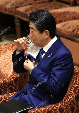 Former Japanese Prime Minister Shinzo Abe drinks water as he apologizes his false statements to parliament at Lower House's house management committee session at the National Diet in Tokyo on Friday, December 25, 2020. Prosecutors decided not to indict Abe for his alleged case of illegal payment and prosecutors ended investigation of Abe's scandal.