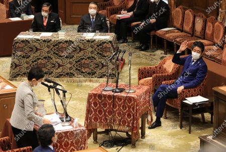 Former Japanese Prime Minister Shinzo Abe (R) raises his hand to answer a question of an opposition lawmaker Kiyomi Tsujimoto as he apologizes his false statements to parliament at Lower House's house management committee session at the National Diet in Tokyo on Friday, December 25, 2020. Prosecutors decided not to indict Abe for his alleged case of illegal payment and prosecutors ended investigation of Abe's scandal.