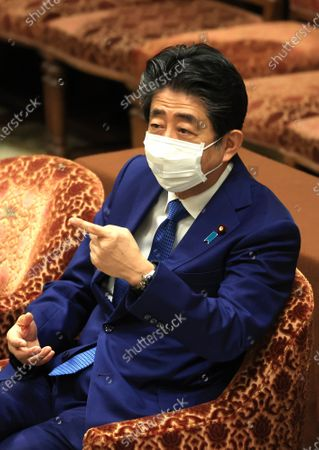 Former Japanese Prime Minister Shinzo Abe reacts to a question of an opposition lawmaker Kiyomi Tsujimto as he apologizes his false statements to parliament at Lower House's house management committee session at the National Diet in Tokyo on Friday, December 25, 2020. Prosecutors decided not to indict Abe for his alleged case of illegal payment and prosecutors ended investigation of Abe's scandal.