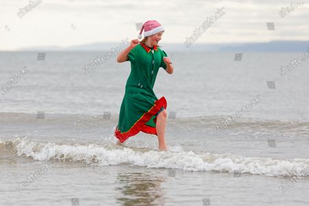 Serena Evans, 11, takes to the sea wearing an elf's outfit and a Santa hat in Porthcawl