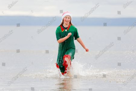Stock Image of Serena Evans, 11, takes to the sea wearing an elf's outfit and a Santa hat in Porthcawl