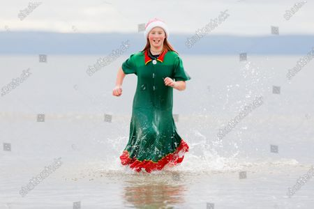 Stock Photo of Serena Evans, 11, takes to the sea wearing an elf's outfit and a Santa hat in Porthcawl