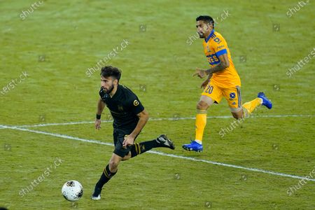 Los Angeles FC forward Diego Rossi, left, moves the ball past Tigres midfielder Javier Aquino (20) during the second half of a CONCACAF Champions League soccer match, in Orlando, Fla