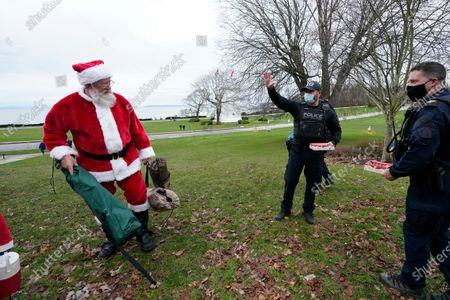 Vancouver Police officer Jordan Stein, center, waves to Santa, also known as Dave Budd, of Surrey, B.C., after Budd crossed from Canada into the U.S. at Peace Arch Historical State Park, in Blaine, Wash. Stein and fellow border enforcement team officers stepped into the park to hand out candy canes. Canadians have routinely been walking across the ditch to meet with sweethearts, friends and family in the U.S. there, many visiting in tents they set-up in the park, where the Washington state park remains open and the nearby, adjacent Peace Arch Provincial Park in Canada remains closed