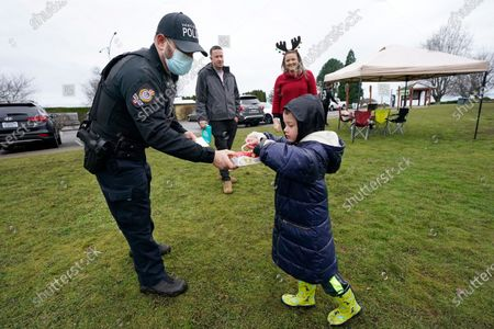 Stock Image of Vancouver Police officer Jordan Stein hands out candy canes at Peace Arch Historical State Park, in Blaine, Wash. Stein and fellow border enforcement team officers stepped into the park to hand out candy on the Christmas holiday. Canadians have routinely been walking across the ditch to meet with sweethearts, friends and family in the U.S. there, many visiting in tents they set-up in the park, where the Washington state park remains open and the nearby, adjacent Peace Arch Provincial Park in Canada remains closed