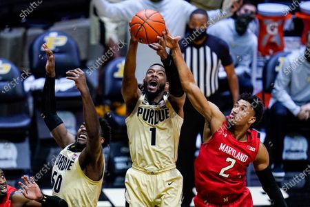 Purdue forward Aaron Wheeler (1) grabs a rebound over teammate Purdue forward Trevion Williams (50) and Maryland guard Aaron Wiggins (2) during the second half of an NCAA college basketball game in West Lafayette, Ind., . Purdue defeated Maryland 73-70