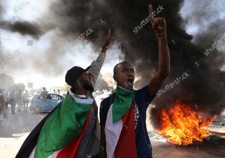 Demonstrator gives a victory sign during a protest, in Khartoum, Sudan, . Protests in Sudan's capital and across the country are demanding a faster pace to democratic reforms, in demonstrations marking the two-year anniversary of the uprising that led to the military's ouster of strongman Omar al-Bashir