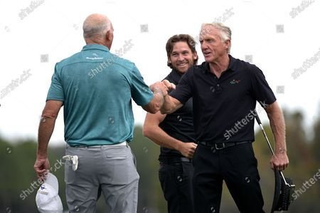 Greg Norman, right, of Australia, and his son Greg Norman Jr. exchange fist bumps with Tom Lehman, left, after finishing on the 18th green during the final round of the PNC Championship golf tournament, in Orlando, Fla