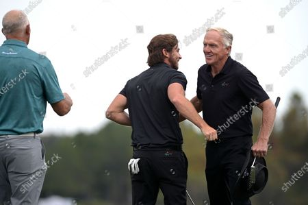 Greg Norman, right, of Australia, embraces his son Greg Norman Jr. as Tom Lehman, left, approaches after finishing on the 18th green during the final round of the PNC Championship golf tournament, in Orlando, Fla