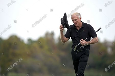 Greg Norman, of Australia, removes his hat after finishing on the 18th green during the final round of the PNC Championship golf tournament, in Orlando, Fla