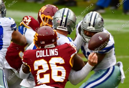 Dallas Cowboys quarterback Andy Dalton (14) fumbles under pressure from Washington Football Team's Landon Collins (26) to set up a Washington safety during the first half of an NFL football game at FedEx Field in Landover, Maryland, on Sunday, October 25, 2020. Photo by David Tulis/UPI