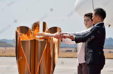 Three-time Olympic gold medalists Tadahiro Nomura(R) and Saori Yoshida light the torch during the Olympic Flame Arrival Ceremony at Japan Air Self-Defense Force (JASDF) Matsushima Base in Higashi-Matsushima, Miyagi prefecture, Japan on Friday, March 20, 2020. Photo by Keizo Mori/UPI