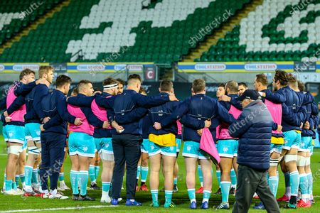 Warriors players form a huddle, as Worcester Warriors director of rugby Alan Solomons looks on