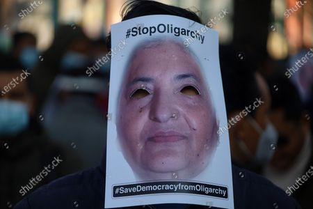 A Civil society activist wear facial masks depicting Nepal's President Bidhya Devi Bhandari on a protest against the Prime minister for taking a step of Parliament abruptly dissolved in Kathmandu on December.