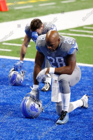 Detroit Lions running back Adrian Peterson (28) and wide receiver Danny Amendola (80) kneel in the end zone prior to an NFL football game against the Tampa Bay Buccaneers, in Detroit