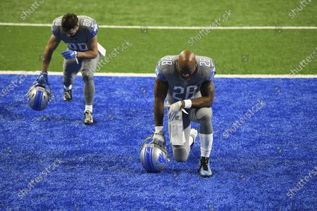 Detroit Lions wide receiver Danny Amendola (80) and running back Adrian Peterson (28) pause to pray before the first half of an NFL football game against the Tampa Bay Buccaneers, in Detroit