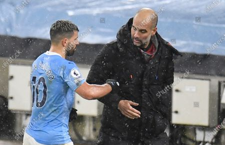 Manchester City's Sergio Aguero (L) shakes hands with manager Pep Guardiola (R) after the English Premier League soccer match between Manchester City and Newcastle United in Manchester, Britain, 26 December 2020.