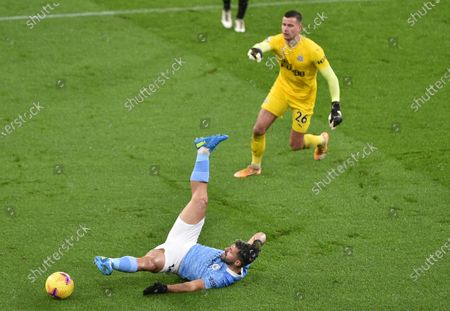 Manchester City's Sergio Aguero falls in a challenge with Newcastle's goalkeeper Karl Darlow during the English Premier League soccer match between Manchester City and Newcastle United at the Etihad stadium in Manchester