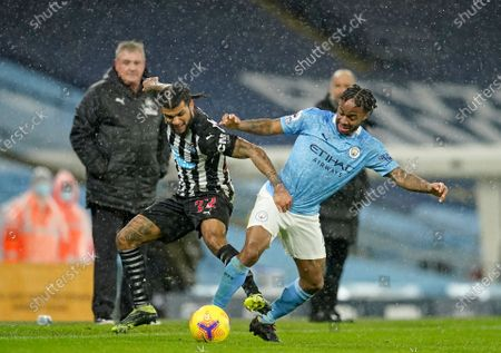 Newcastle's DeAndre Yedlin, left, challenges Manchester City's Raheem Sterling during the English Premier League soccer match between Manchester City and Newcastle United at the Etihad stadium in Manchester