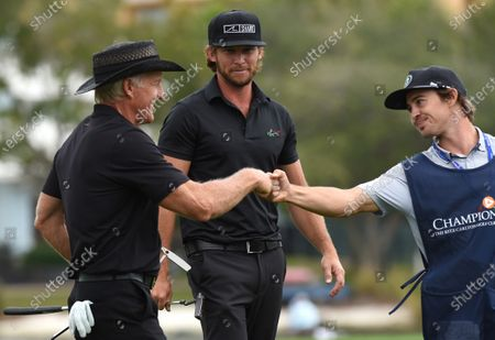 Australian Greg Norman (left) and his son, Greg Norman Jr. fist bump with a caddie after completing the final round at the PNC Championship golf tournament at the Ritz-Carlton Golf Club.  On Christmas Day, Norman posted a photo on Instagram from a hospital bed where he was being treated for COVID-19 symptoms. Norman's son also posted a photo on Instagram, stating that he and his fiancée have tested positive for the COVID-19 virus.
