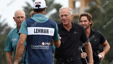 Australian Greg Norman (2nd r), his son, Greg Norman Jr. (r), and Tom Lehman (left) fist bump with each other after completing the final round at the PNC Championship golf tournament at the Ritz-Carlton Golf Club.  On Christmas Day, Norman posted a photo on Instagram from a hospital bed where he was being treated for COVID-19 symptoms. Norman's son also posted a photo on Instagram, stating that he and his fiancée have tested positive for the COVID-19 virus.