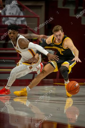 Iowa forward Jack Nunge (2) battles Minnesota guard Marcus Carr (5) for the ball in overtime of an NCAA college basketball game, in Minneapolis. Minnesota won 102-95 in overtime