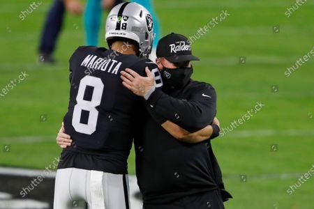 Las Vegas Raiders quarterback Marcus Mariota (8) embraces Las Vegas Raiders head coach Jon Gruden before an NFL football game, in Las Vegas
