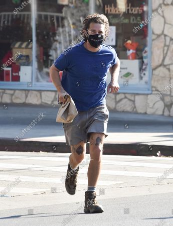 Stock Image of Shia LaBeouf takes a jog across the street in his hiking boots carrying a brown paper bag