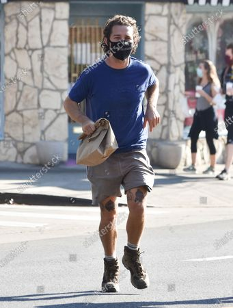 Shia LaBeouf takes a jog across the street in his hiking boots carrying a brown paper bag