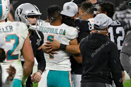 Miami Dolphins quarterback Tua Tagovailoa (1) embraces Las Vegas Raiders quarterback Marcus Mariota (8) after an NFL football game, in Las Vegas