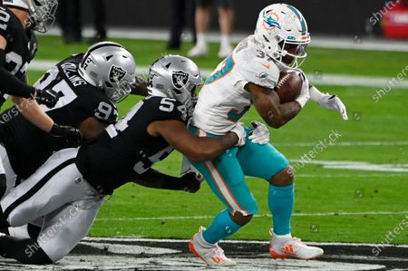 Las Vegas Raiders middle linebacker Raekwon McMillan (54) tackles Miami Dolphins running back Myles Gaskin (37) during the first half of an NFL football game, in Las Vegas
