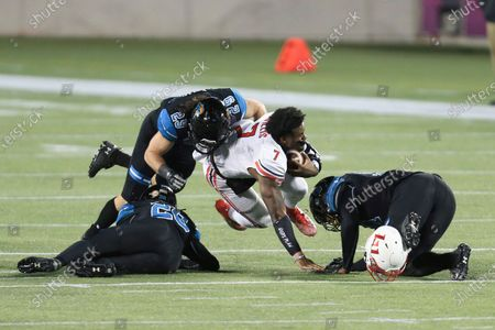 Liberty quarterback Malik Willis (7) loses his helmet while being tackled by Coastal Carolina linebacker Silas Kelly (29) and others during the first half of the Cure Bowl NCAA college football game, in Orlando, Fla. Kelly was penalized on the play