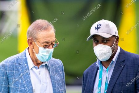 From left, Miami Dolphins Chairman of the Board/Managing General Partner Stephen Ross and Miami Dolphins General Manager Chris Grier wear masks as they talk on the sidelines before the Dolphins take on the New England Patriots during an NFL football game, in Miami Gardens, Fla
