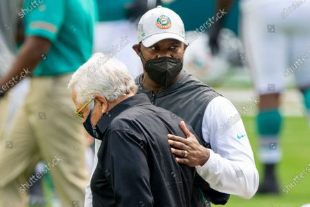 Miami Dolphins head coach Brian Flores (rear), and New England Patriots owner Robert Kraft wear masks as they speak on the field before an NFL football game, in Miami Gardens, Fla