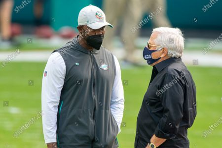 Miami Dolphins head coach Brian Flores (left), and New England Patriots owner Robert Kraft wear masks as they speak on the field before an NFL football game, in Miami Gardens, Fla