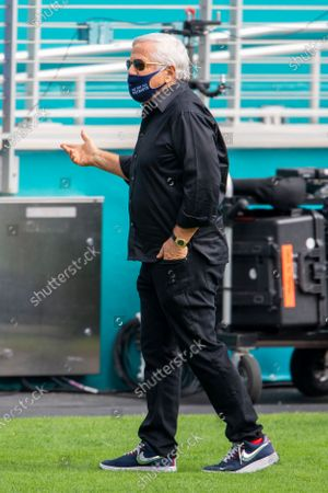 New England Patriots owner Robert Kraft wears a mask as he gestures on the sidelines before the Patriots take on the Miami Dolphins during an NFL football game, in Miami Gardens, Fla
