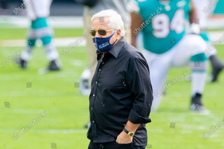 New England Patriots owner Robert Kraft wears a mask on the field before the Patriots take on the Miami Dolphins during an NFL football game, in Miami Gardens, Fla