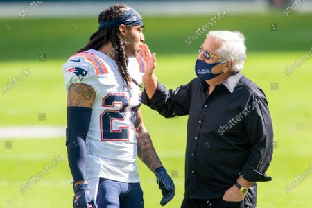 New England Patriots owner Robert Kraft wears a mask on the field as he talks with New England Patriots cornerback Stephon Gilmore (24) before the Patriots take on the Miami Dolphins during an NFL football game, in Miami Gardens, Fla