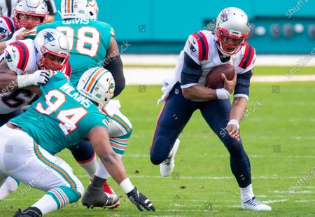 Stock Photo of New England Patriots quarterback Cam Newton (1) runs with the ball past Miami Dolphins defensive tackle Raekwon Davis (98) and Miami Dolphins defensive tackle Christian Wilkins (94) during an NFL football game, in Miami Gardens, Fla