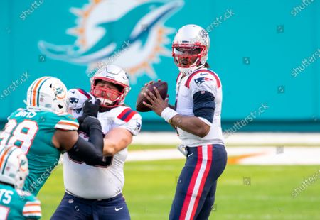 New England Patriots quarterback Cam Newton (1) looks to pass the ball as New England Patriots center David Andrews (60) blocks Miami Dolphins defensive tackle Raekwon Davis (98) during an NFL football game, in Miami Gardens, Fla