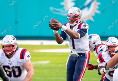 New England Patriots quarterback Cam Newton (1) takes the hike of the ball from New England Patriots center David Andrews (60) as the Patriots take on the Miami Dolphins during an NFL football game, in Miami Gardens, Fla