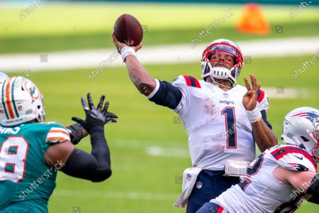 Stock Image of New England Patriots quarterback Cam Newton (1) throws the ball under pressure from Miami Dolphins defensive tackle Raekwon Davis (98) during an NFL football game, in Miami Gardens, Fla